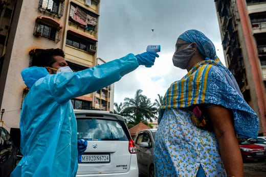 A health worker (L) wearing Personal Protective Equipment (PPE) takes the temperature of a resident during a door-to-door medical screening drive for the COVID-19 coronavirus, at a residential complex in Mumbai on July 20, 2020. - Coronavirus cases in India passed one million on July 17, official data showed as authorities struggle to check the spread of the deadly pandemic across the world's second-most populous nation.