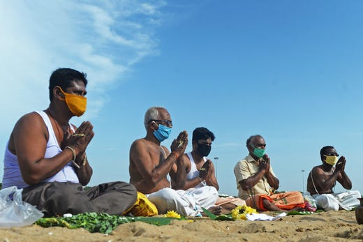 Hindu devotees offer food and prayers as they perform 'Tarpan' rituals that are believed to ensure peace and happiness to the souls of one's ancestors, at Marina beach in Chennai on July 20, 2020.