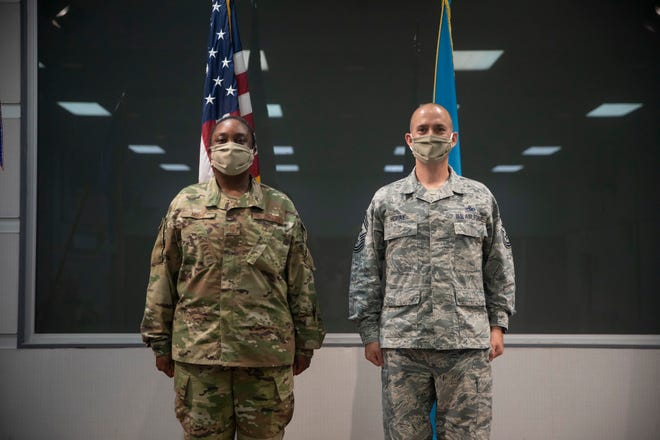 Outgoing 166th Airlift Wing Command Chief Master Sgt. William J. Horay Jr., right, stands at attention with incoming Command Chief Master Sgt. Robbin D. Moore.