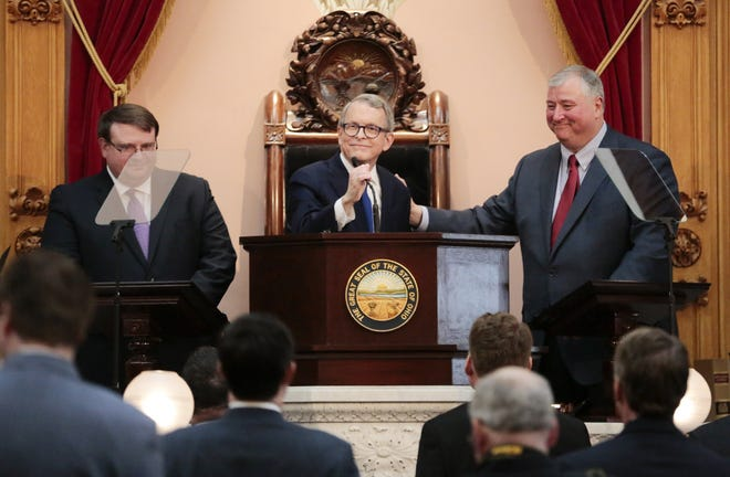Ohio Gov. Mike DeWine takes the podium as then-House Speaker Larry Householder, right, and Senate President Larry Obhof, left, greet him during his first State of the State address on Tuesday, March 5, 2019.
