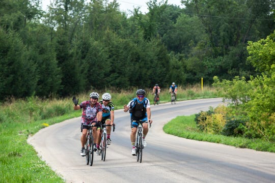 Geoff Perrill and Josh Schamberger pedal ahead of RAGBRAI Director Dieter Drake as they ride along Sugar Bottom Road, Tuesday, July 21, 2020, in Johnson County, Iowa.