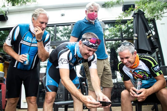 Josh Schamberger, second from left, shows RAGBRAI Director Dieter Drake, right, a video while visiting with members of eastern Iowa RAGBRAI groups, Tuesday, July 21, 2020, at Big Grove Brewpub in Solon, Iowa.