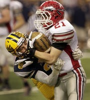 Ithaca's Eli Villalobos puts a hit on Clinton's Collin Poore during the MHSAA Division 6  Championship at Ford Field in Detroit, Nov. 29, 2013.