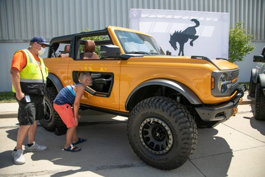 Ryan Vetter of Ford communications, from Taylor, left, looks on as his son Carson-Ryan Vetter, 9, checks out the new 2-door 2021 Ford Bronco on Tuesday, July 21, 2020. Ford employees got an opportunity to check out the new 2- and 4-door Ford Broncos they will be building later this year at the Michigan Assembly Plant in Wayne.