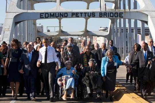 """In this March 7, 2015 photo, singing """"We Shall Overcome,"""" President Barack Obama, third from left, walks holding hands with Amelia Boynton, who was beaten during """"Bloody Sunday,"""" as they and the first family and others including Rep. John Lewis, D-Ga, left of Obama, walk across the Edmund Pettus Bridge in Selma, Ala., for the 50th anniversary of """"Bloody Sunday,"""" a landmark event of the civil rights movement. Some residents in the landmark civil rights city of Selma, Ala., are among the critics of a bid to rename the historic bridge where voting rights marchers were beaten in 1965."""