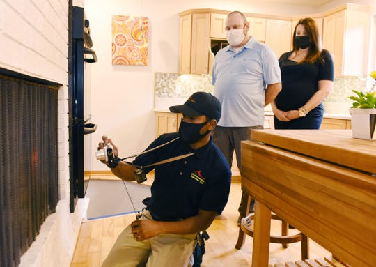 Charles Shaver, left, inspects a house Tuesday as new homeowner Mike McDevitt and real estate agent Christina Gennari watch. The McDevitts lost out on two bids  for houses. Then they put in an offer of$18,000 above the $249,500 asking price for this West Bloomfield Township home. This time, they won.