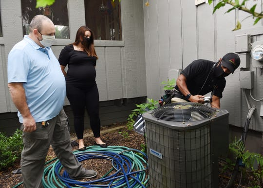 New home owner Mike Mcdevitt, left, and real estate agent Christina Gennari watch as inspector Charles Shaver of CNM Inspection Services looks at the air conditioner of a home bought by Mr. Mcdevitt, Tuesday, July 21, 2020, in West Bloomfield.