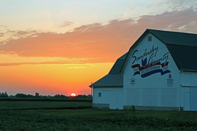 The sun rises along U.S. 20 near Lindsey. Barns around Sandusky County have been painted to celebrate the county's bicentennial this year.