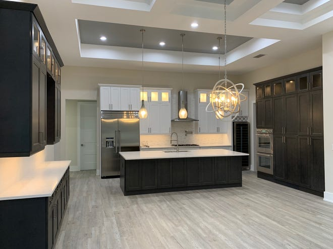 The kitchen in the recently completed custom home by Cintron Custom Builders boasts a ten foot island that allows for comfortable, large family dining.