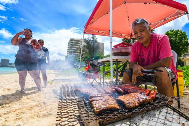 Ken Lujan, right, watches over the grilling of ribs and sausages as he, his wife and their grandchildren spend part of their Liberation Day holiday on the sands and in the waters of Matapang Beach in Tumon on July 21, 2020.