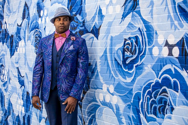 Derrick Clarkson models a cobalt and pastel floral Tallia sport coat, subtle navy plaid vest, raspberry shirt, hand-crafted harwood bow tie, lapel posey, pocket square and straw fedora during a Kentucky Derby fashion shoot with stylist Jo Ross at Churchill Downs. March 11, 2020