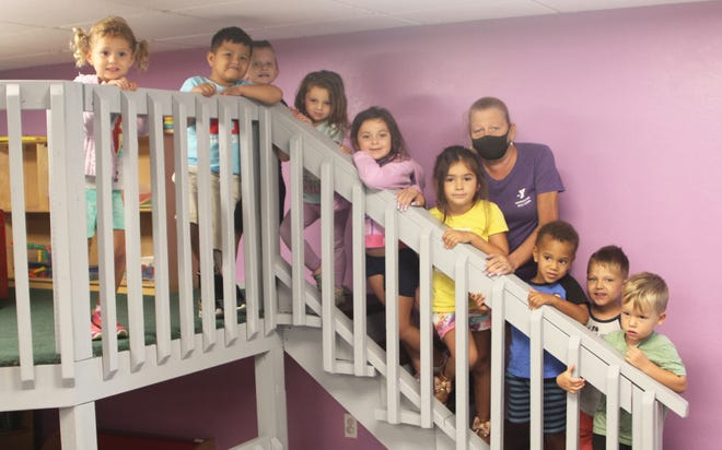 Kelly O'Connor poses earlier this week with some of her young early learning (pre-K) children.