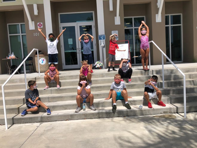 Wearing face coverings at the Marco Island campus, kids spell YMCA with their bodies during summer camp on July 9, 2020.