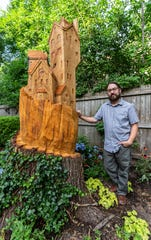 Artist Jeremy Wolf stands with the castle-like village he carved from a 200-year-old oak tree in the backyard of Ann and Morgan White's home in Whitefish Bay. Visit jeremywolf.com to view more of Jeremy's work.