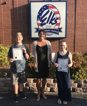 Local winners of the 2019-2020 Arkansas State Elks Americanism Essay Contest were recently honored during an awards banquet at the Mountain Home Elks Lodge. The sixth-grade winners were Konnor Brewer, who took first in the state certificate and won $200; and Symphony Fox, who was third in the state certificate and won $100. Their essays were chosen from over 270 essays locally and then competed on a statewide level. Konnor's essay will now go on to compete for national honors. This is the sixth consecutive year that Pinkston Middle School students have won the state contest. Pictured are (from left) Konnor Brewer, Vonya Schaufler, sixth-grade teacher and Mountain Home Elks Americanism chairman; and Symphony Fox.