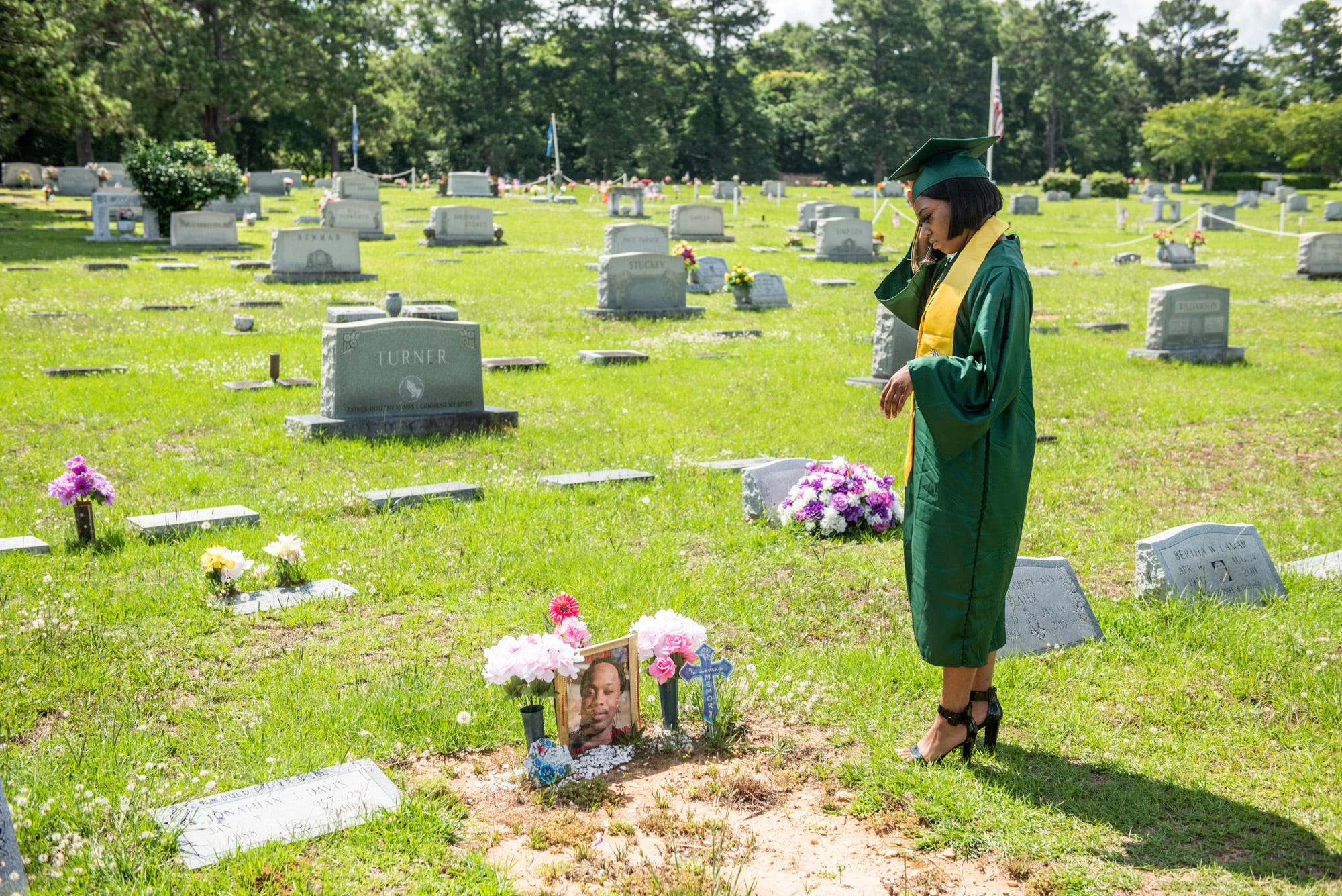 Helen Brown visits the gravesite of her boyfriend, Ty'Riq Moon, after her graduation at Montgomery Memorial Cemetery in Montgomery, Ala., on Thursday, June 4, 2020. Moon was shot and killed at the Madison Ave. McDonalds in September 2019. Brown had promised Moon she was going to graduate and wanted him to see her in the cap and gown.