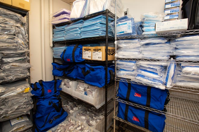 Protective gowns, masks and other personal protective equipment is stacked in preparation for use by those caring for patients with coronavirus infection.