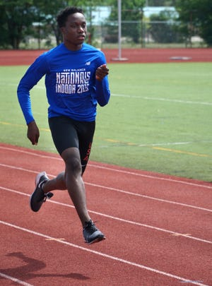 With both feet well off the track Brother Rice athelte Udodi Onwuzurike sprints down the lane at Southfield Lathrup High on July 21, 2020.
