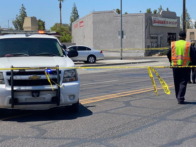 Police investigate a car crash at a Phoenix bus stop that killed a man and injured two bystanders on July 21, 2020.