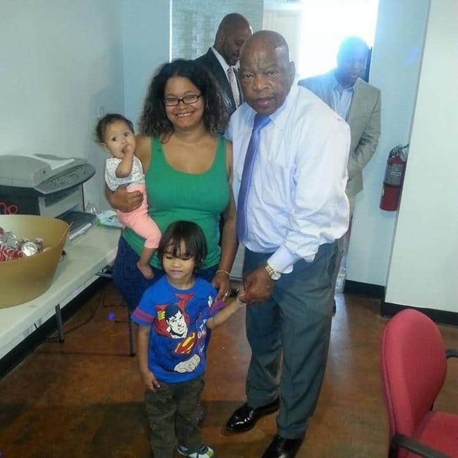 Natacha Chavez, holding daughter Amelia, 6 months, with son Alejandro, 3, and Congressman John Lewis.