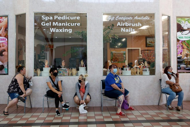 In this May 6, 2020, file photo customers wait for to get their nails done at the Nail Tech salon in the Yuba Sutter Mall in Yuba City. Californians with unruly hair or those needing skin care, nail care or massages in counties on the restrictive watch list still will be able to get some services outdoors even during the current surge in coronavirus cases, officials said Monday, July 20, 2020.