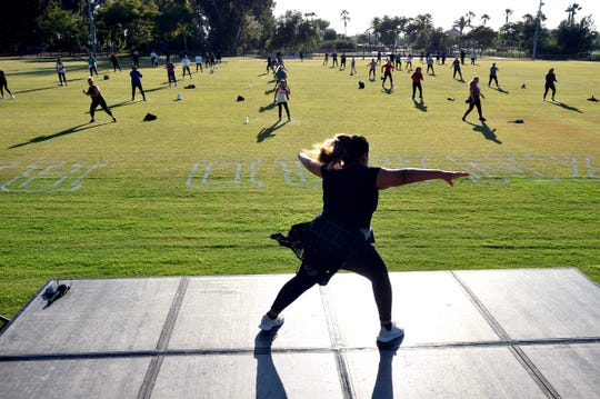 Melizza Ambriz, 26, leads a portion of a free, outdoor Zumba class at Oxnard College Park on Monday, July 20, 2020. The city used its new marking robot to create social distancing circles for outdoor Zumba and yoga classes during the ongoing pandemic.
