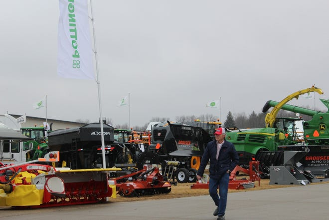 A farmer walks past a large display of farm equipment at a Wisconsin Public Service farm show in 2018. Farm shows across the country have been cancelled due to the coronavirus pandemic, robbing dealerships of the opportunity to get their wares in front of the public.