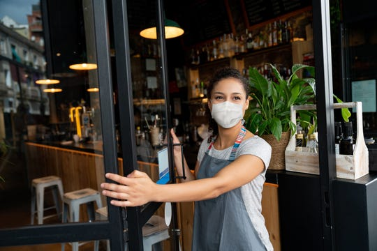 A business owner opens the door at a cafe wearing a facemask to curb the spread of coronavirus.