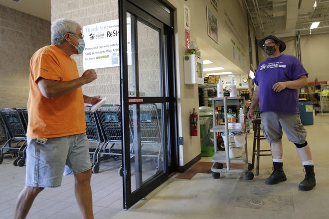 Habitat ReStore East employee Jason Hoyt, right, is stationed at the entrance of the Appleton store to make sure customers are wearing masks. Here, he greets customer Victor Briones of Menasha. Hoyt offers masks to customers who don't have one.