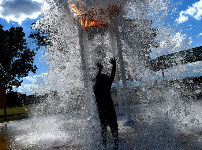 Paizly Lopez, 7, raises her hands as the bucket drops water on her at the Stevenson Park Splash Pad in Abilene. Local splash pads are checked daily for water quality.
