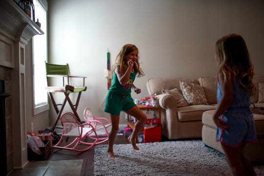 Ada Perrault, 7, left, dances to music in the living room with her sister, Juliet, 3, at their home in Clarksville, Tenn., on Tuesday, July 21, 2020.