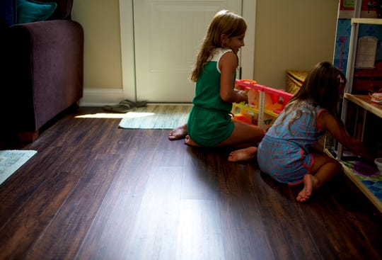 Sisters Ada, 7, left, and Juliet Perrault, 3, play with dolls in the corner of their basement Tuesday, July 21, 2020.