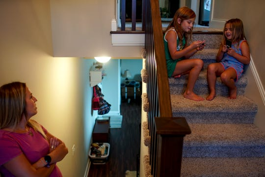 Anne Perrault hangs out with her daughters, Ada, 7, and Juliet, 3, in the stairwell while the sisters play on iPods at their Clarksville home Tuesday, July 21, 2020.