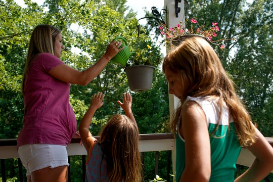 Anne Perrault waters plants with her daughters, Juliet, 3, center, and Ada, 7, at their home in Clarksville, Tenn., on Tuesday, July 21, 2020.