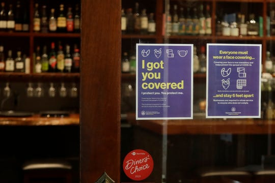 Signs advising social distancing and wearing face masks are posted on a door of The Barrel Room restaurant during the coronavirus outbreak in San Francisco, Tuesday, July 14, 2020.