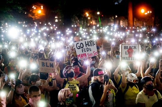 Hundreds of Black Lives Matter protesters hold their phones aloft on Monday, July 20, 2020, in Portland, Ore.