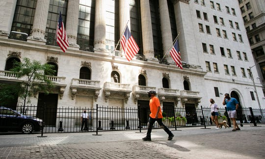 People walk by the New York Stock Exchange, Tuesday, July 21, 2020.