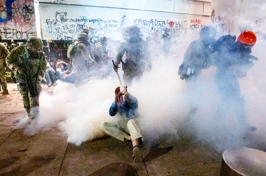 Federal officers use chemical irritants and crowd control munitions to disperse Black Lives Matter protesters outside the Mark O.