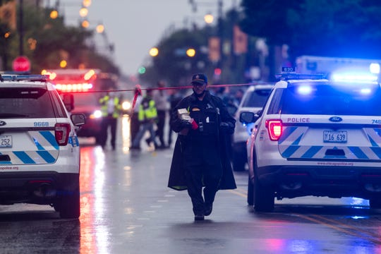 Chicago police investigate the scene of a mass shooting where more then a dozen people were shot Tuesday in the Gresham neighborhood of Chicago.