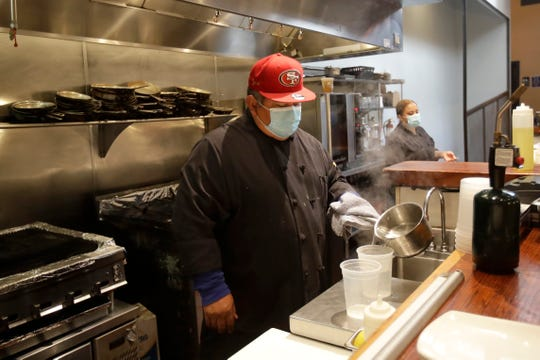 Jose Peraza, sous chef at The Barrel Room, wears a mask while working at the restaurant in San Francisco, Tuesday, July 14, 2020.