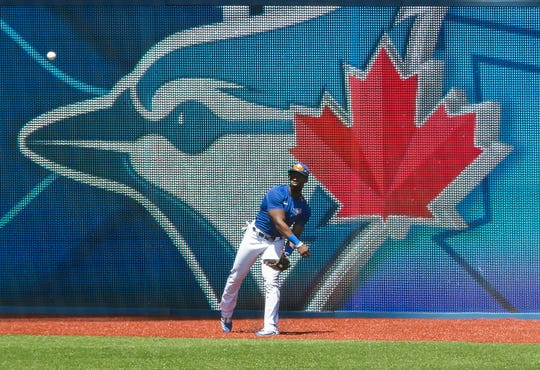 Toronto Blue Jays outfielder Jonathan Davis throws the ball back after making a catch during live batting practice at baseball training camp Monday in Toronto.