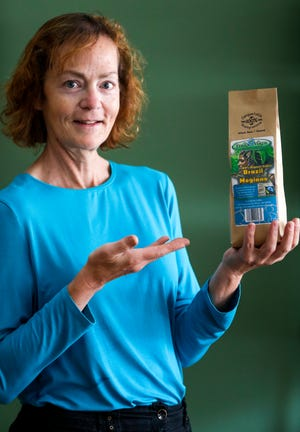 Heather Herdman holds up Brazil Magiano's 100% Organic Coffee on Wednesday, July 22, 2020. Herdman is the owner of Sweet Willow Herbal Co-op located at 327 Main Ave., De Pere, Wis. Ebony Cox/USA TODAY NETWORK-Wisconsin