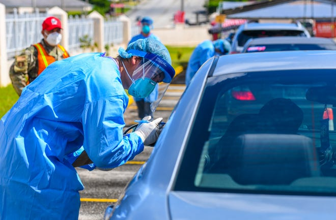 Kai Akimoto records information from a driver requesting to be tested for COVID-19 during a drive-through extended outreach in the parking lot of Tamuning Elementary School in this July 22 file photo. PDN FILE PHOTO