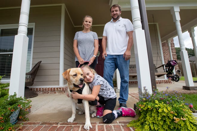 "Karon and Jimmy Reed with their daughter Ava, 8, and her English Labrador service dog Maggie at the family's Arlington home on Wednesday, July 22, 2020. Last year, the Reed family received Maggie, through trainer Jeff Tawater and his company K9 Direction after an outpouring of community support helped raise the over $10,000 to acquire her. The Reed family says Tawater has since failed to fulfill his training duties and though the family is interested in continuing to work with Maggie, though she currently ""provides no service"" for Ava."