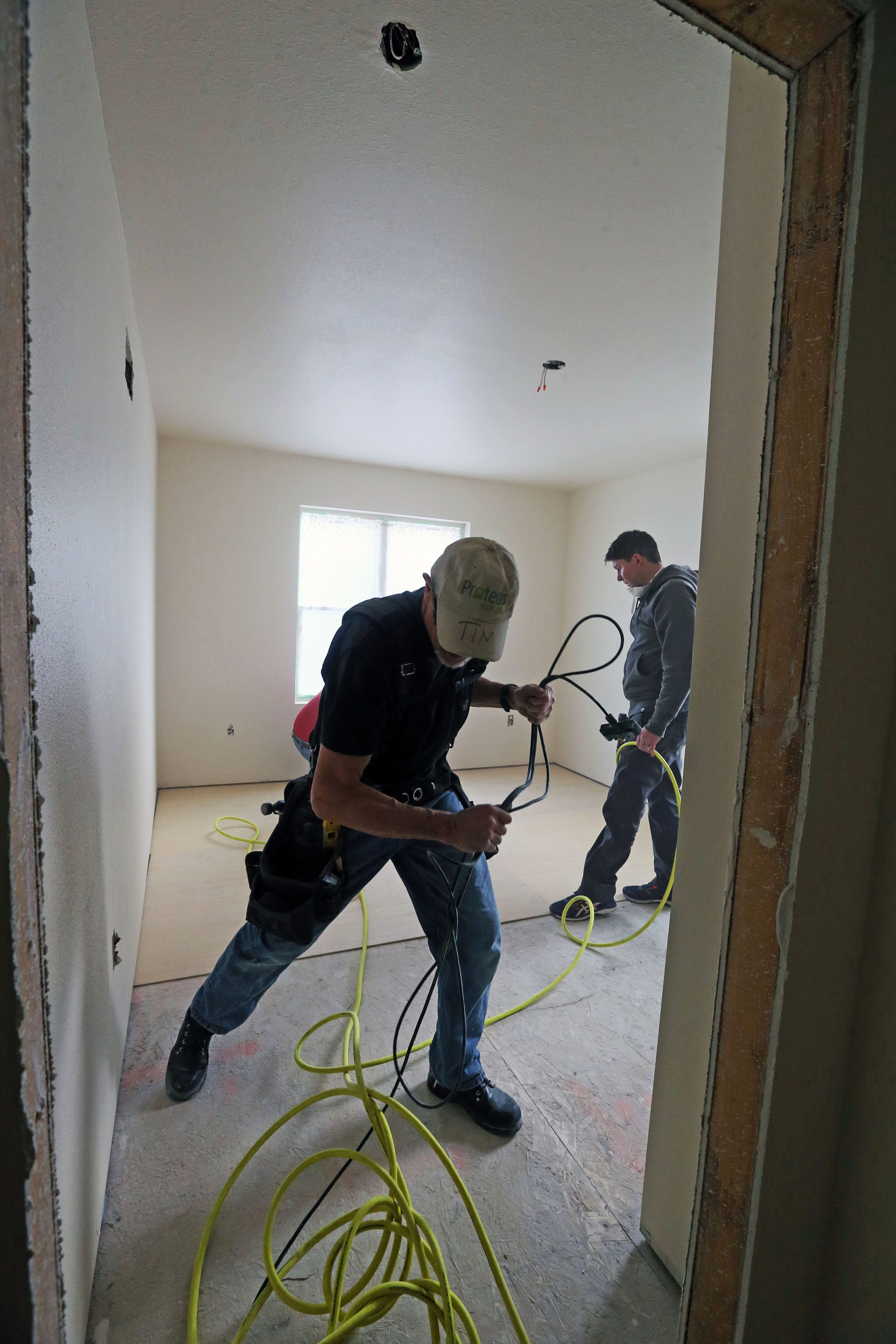 Tim Wayman, foreground, and Dave Larson do flooring work on a Habitat for Humanity home at 2223 N. 28th St., Milwaukee, on Jan. 20.
