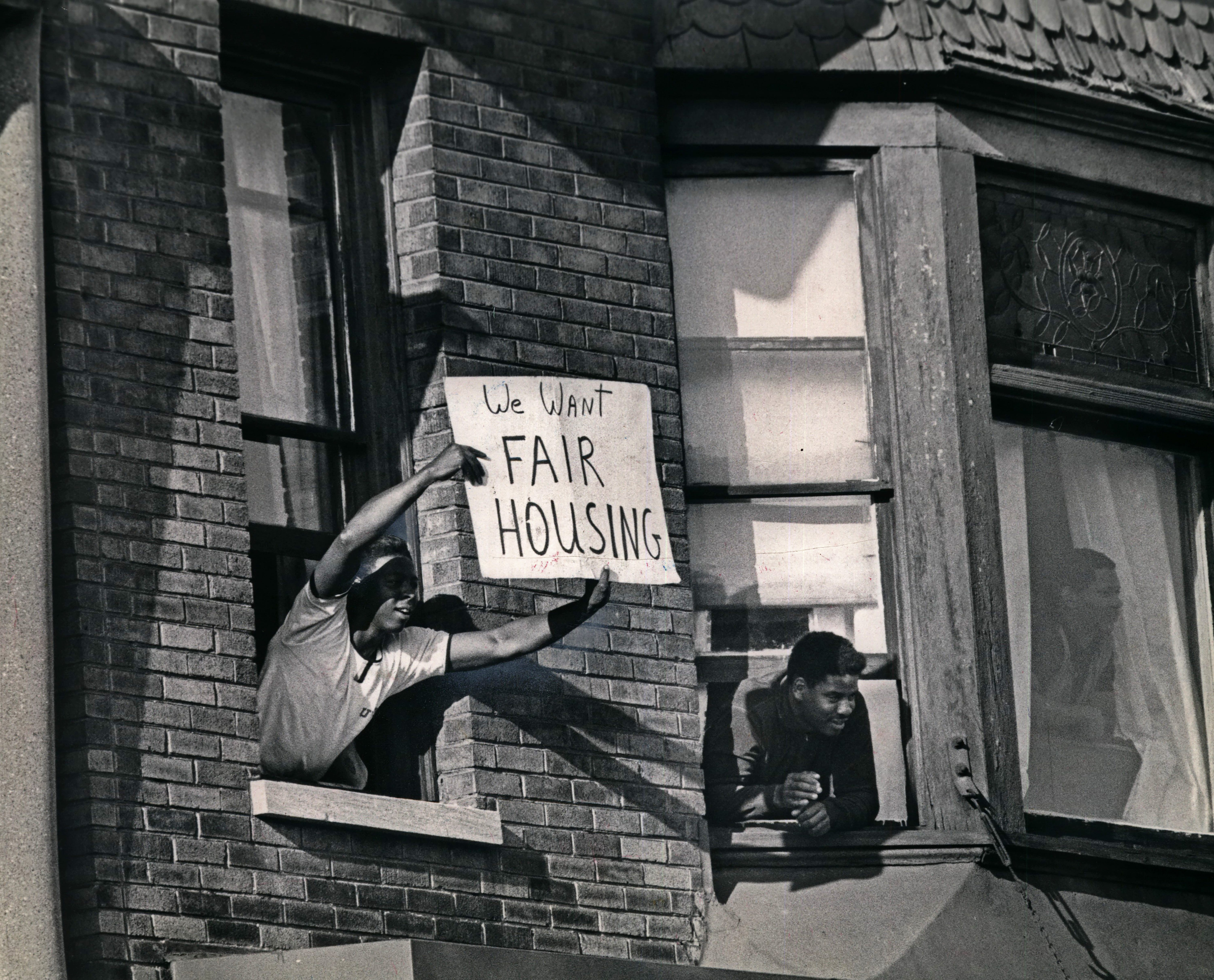As civil rights demonstrators march near West Center and North 14th streets, an apartment dweller flashes a sign calling attention to the demand for open housing legislation in this Sept. 3, 1967,  photo.