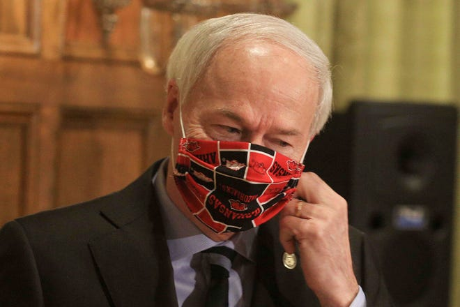 In this April 27, 2020 file photo, Gov. Asa Hutchinson takes off his Arkansas Razorbacks face mask as he arrives for the daily coronavirus briefing at the state Capitol in Little Rock. The governor said Tuesday that he was standing by his plan to return to in-class instruction in late August.
