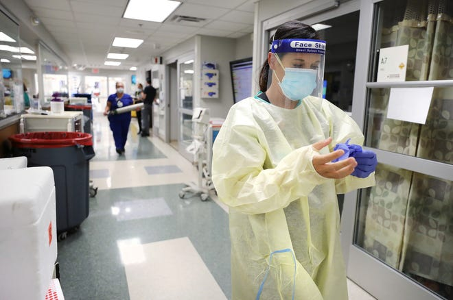 Holly Beth Jones, a nurse in Vanderbilt's emergency department, finishes putting on personal protective equipment July 21, 2020, in Nashville, Tennessee.