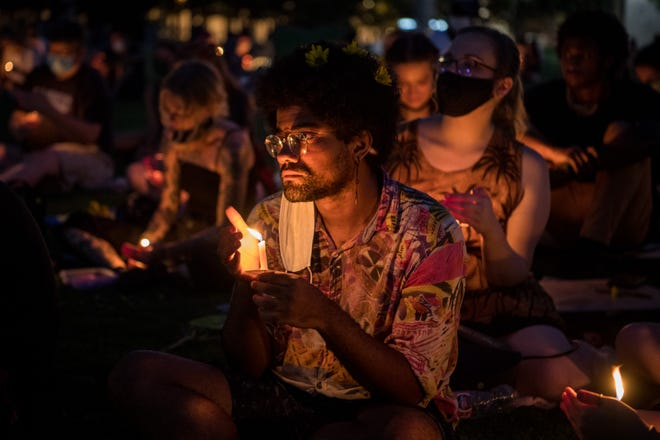 Gabriel Vaden, of Nashville, holds a candle during a vigil at Public Square Park in Nashville on Tuesday.