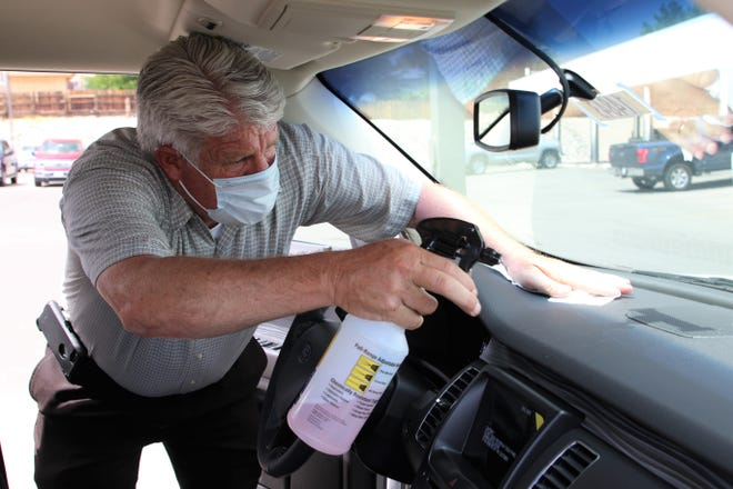 Ziems Ford Corners salesman Carroll Carter sanitizes the dashboard of a vehicle in the dealership's inventory on Monday, July 20, 2020, in Farmington.